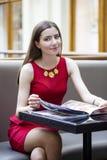 La muchacha hermosa que se sienta en un café y considera el menú Foto de archivo libre de regalías