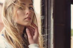 La muchacha hermosa que se sienta en un tren abandonado y un fuerte viento desarrolla su pelo Fotos de archivo libres de regalías