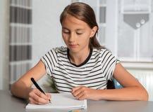 La muchacha hermosa que trabaja en su escuela proyecta en casa imagen de archivo libre de regalías