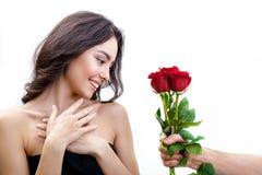 La muchacha hermosa recibe tres rosas rojas Foto de archivo libre de regalías