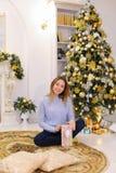 La muchacha hermosa recibió el regalo el la víspera de la Navidad y las actitudes y s Fotos de archivo libres de regalías