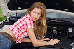 La muchacha hermosa repara el coche foto de archivo libre de regalías