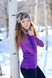 La muchacha hermosa se coloca cerca del abedul en invierno Fotografía de archivo