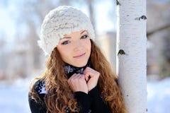 La muchacha hermosa se coloca cerca del abedul en invierno Fotos de archivo libres de regalías