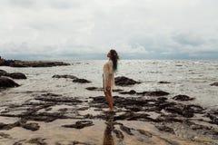 La muchacha hermosa se coloca en el agua en la playa, manojos hermosos alrededor Foto de archivo