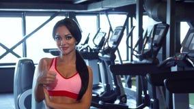 La muchacha hermosa se coloca en el gimnasio y muestra los pulgares para arriba almacen de metraje de vídeo