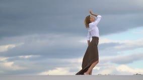 La muchacha hermosa se coloca en la arena en un fondo de nubes, tiroteo a cámara lenta metrajes