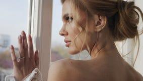 La muchacha hermosa se coloca en la ventana y las miradas en la distancia almacen de metraje de vídeo