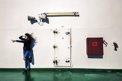 La muchacha hermosa se está colocando al lado de la pared blanca en la cubierta Foto de archivo libre de regalías