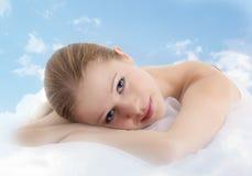 La muchacha hermosa se está reclinando en las nubes Fotografía de archivo