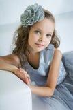 La muchacha hermosa se está sentando en el sofá Fotos de archivo