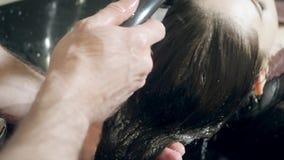 La muchacha hermosa se lava el pelo antes de un corte de pelo en un salón de belleza pelo que se lava en una peluquería, muchacha metrajes