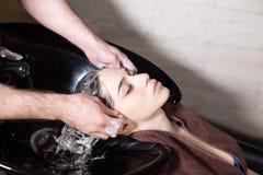 La muchacha hermosa se lava el pelo antes de un corte de pelo en un salón de belleza pelo que se lava en una peluquería, muchacha Fotografía de archivo