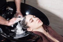 La muchacha hermosa se lava el pelo antes de un corte de pelo en un salón de belleza pelo que se lava en una peluquería, muchacha Foto de archivo libre de regalías