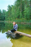 La muchacha hermosa se sienta en el registro por el río Imagen de archivo