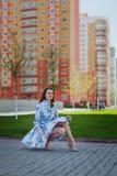 La muchacha hermosa se sienta en el vestido corto azul levantado por el viento contra la perspectiva de altas casas Foto de archivo libre de regalías