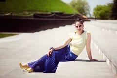 La muchacha hermosa se sienta en las escaleras de piedra ásperas con mirada ideal Foto de archivo libre de regalías