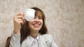 La muchacha hermosa se sienta en silla en café que habla y de consumición de la oficina de la taza blanca el empresario de sexo f imagen de archivo