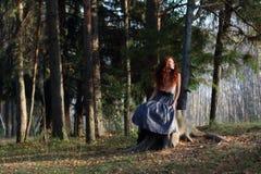 La muchacha hermosa se sienta en tocón en bosque del otoño Foto de archivo