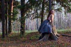 La muchacha hermosa se sienta en tocón grande y presenta en el viento Imagenes de archivo