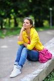 La muchacha hermosa se sienta en un parque con la mano en la barbilla Fotografía de archivo libre de regalías