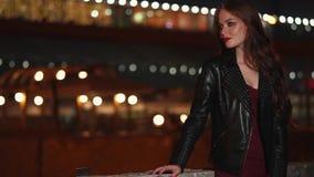 La muchacha hermosa sola se está colocando en una calle de la ciudad de la noche en verano metrajes