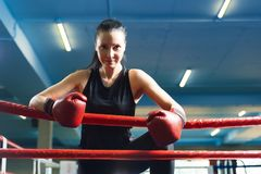 La muchacha hermosa sonríe en un ring de boxeo y guantes imagen de archivo libre de regalías