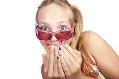 La muchacha hermosa sonriente cierra su boca con las manos Foto de archivo libre de regalías