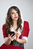 La muchacha hermosa sonriente de Papá Noel en sudadera con capucha roja viste mecanografiar en el teléfono móvil que mira la cáma Imágenes de archivo libres de regalías