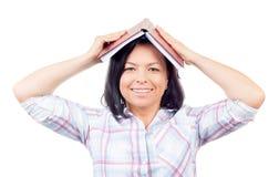 La muchacha hermosa sonriente del ollege del ¡de los jóvenes Ð cubre su cabeza con el libro Fotos de archivo