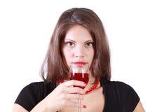 La muchacha hermosa sostiene el vidrio de vino rojo y preparado para beber  Foto de archivo