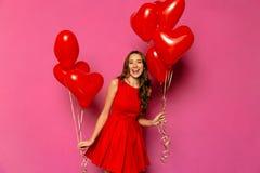 La muchacha hermosa sostiene los globos en dos manos el día del ` s de la tarjeta del día de San Valentín Imagenes de archivo
