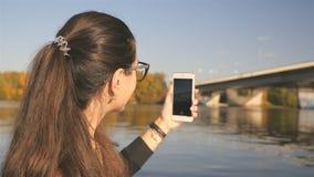 La muchacha hermosa toma imágenes de la naturaleza Río con un puente El paisaje pintoresco Filmación en el teléfono lento almacen de metraje de vídeo