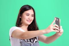 La muchacha hermosa toma la imagen con el teléfono, sobre verde Fotos de archivo libres de regalías
