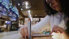 La muchacha hermosa triste con el pelo rizado en un restaurante está haciendo compras en línea almacen de video