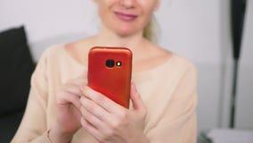 La muchacha hermosa utiliza un smartphone celular mientras que se sienta en la sala de estar por la tarde Mujer joven sonriente f metrajes
