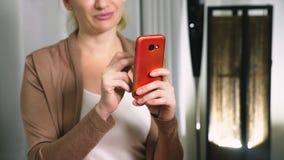 La muchacha hermosa utiliza un smartphone celular mientras que se sienta en la sala de estar por la tarde Mujer joven sonriente f almacen de video