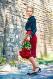La muchacha hermosa y atractiva con un ramo de rosas rojas se coloca en el fondo de una pared de ladrillo vieja imagen de archivo
