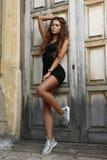 La muchacha hermosa y atractiva joven con el cuerpo atractivo bronceado sol delgado es presentación al aire libre en los pasos Imágenes de archivo libres de regalías