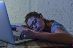 La muchacha hermosa y cansada joven del estudiante que dormía tomando una siesta que mentía en el escritorio casero del ordenador Fotos de archivo libres de regalías