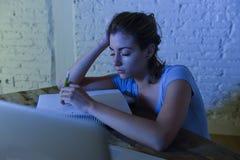 La muchacha hermosa y cansada joven del estudiante que dormía tomando una siesta que mentía en el escritorio casero del ordenador Foto de archivo