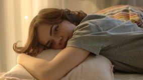 La muchacha hermosa, y romántica miente en la cama La mujer joven coloca en la cama La mujer coloca para descansar metrajes