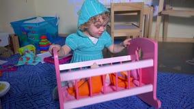 La muchacha hiperactiva balancea su muñeca áspero en cama del juguete almacen de video
