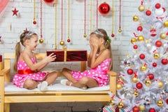 La muchacha hizo una pequeña hermana una sorpresa bajo la forma de regalo Foto de archivo