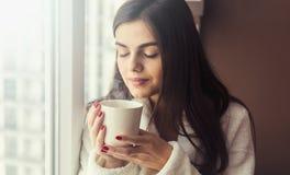 La muchacha huele el café fotos de archivo