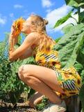 La muchacha huele una flor fotografía de archivo libre de regalías