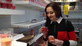 La muchacha huele velas perfumadas y elige de lo que ella tiene gusto almacen de metraje de vídeo