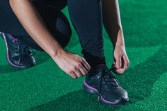 La muchacha implica cordones antes de entrenar en un gimnasio en un piso verde, crossfit Cierre para arriba fotografía de archivo