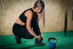 La muchacha implica cordones antes de entrenar en un gimnasio en un piso verde, crossfit Cierre para arriba fotos de archivo
