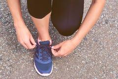 La muchacha implica cordones en zapatillas de deporte en el camino mientras que activa, pierna y las zapatillas de deporte, image Foto de archivo